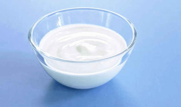 A bowl of greek yogurt sitting on a blue surface