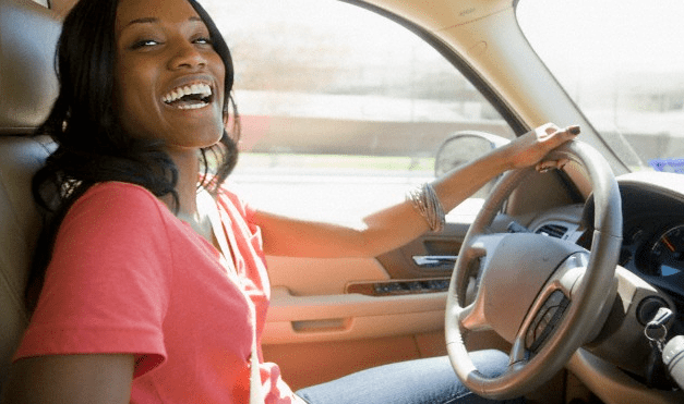 A woman smiling in her car