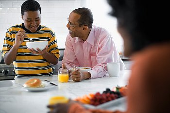 A teenager eating in the kitchen with his parents