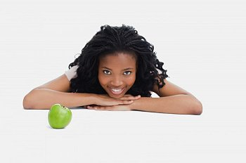 A woman smiling near a green apple on a white surface