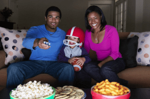 A family watching football on TV with snacks on a table
