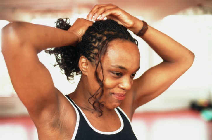 African American Black woman with braids putting hair in ponytail