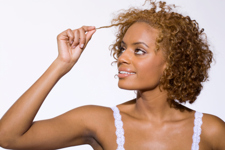 African American Black woman looking at her natural curly hair