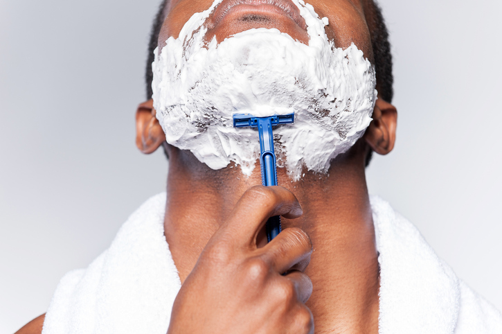Close up of young African man shaving his face while standing against grey background