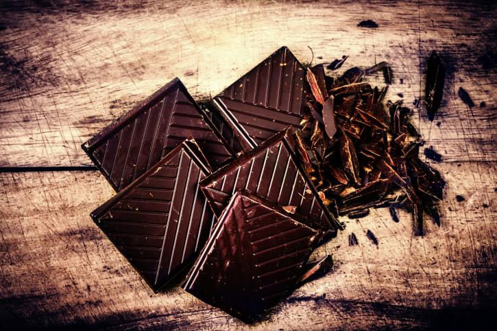 Chopped Chocolate Bar on wooden background closeup. Broken dark