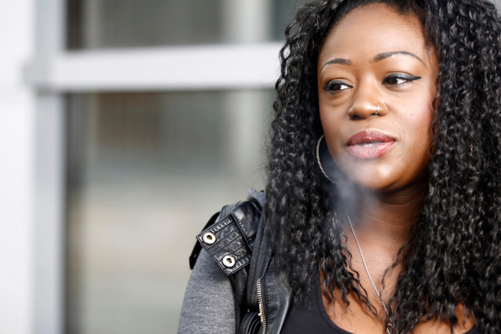 african american woman blowing out cigarette smoke
