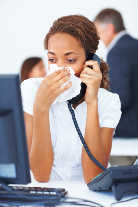 sick woman work blowing nose