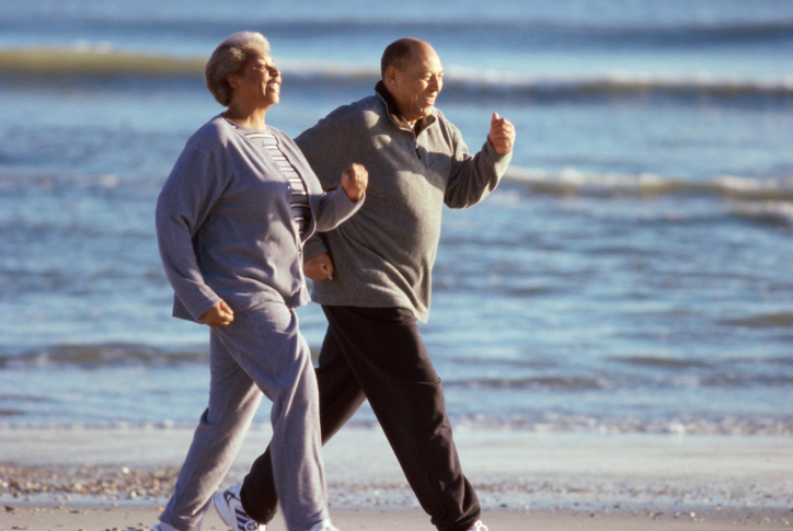 African American senior couple walking on the beach