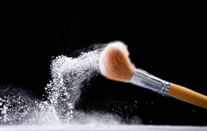 makeup brush dusted in a powder