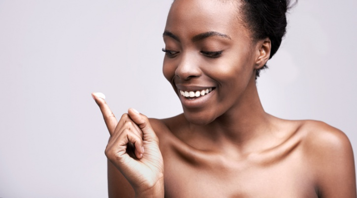 african american woman holding face cream