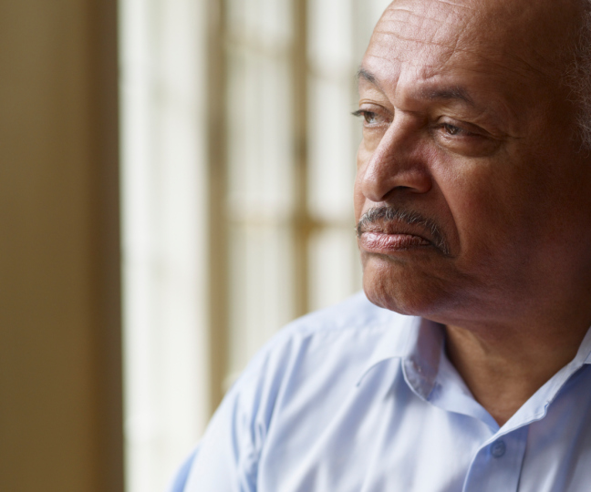 Older African American man looking out window
