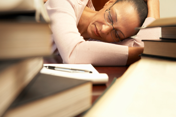 tired woman sleeping on a crowded desk