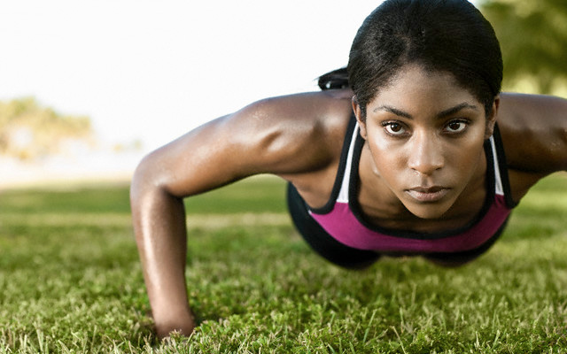 fit black woman doing push up outside on grass