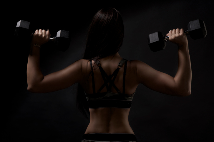 back profile of woman with weights in both hands