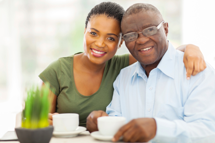 African American Black young woman and older father having coffee