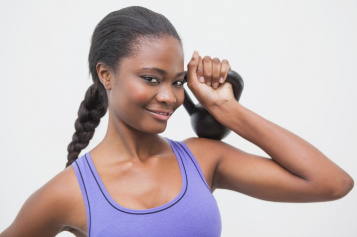 African American woman lifting small kettlebell