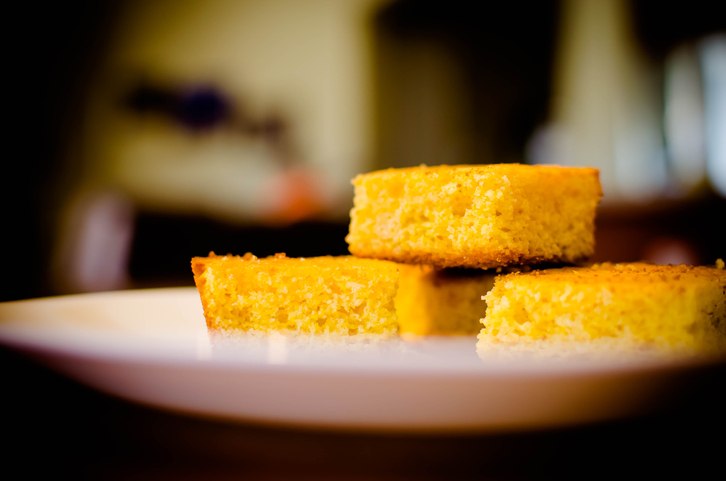 Yellow corn bread on a white plate. Kitchen in background.