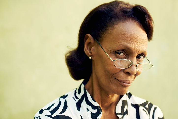 Portrait of confident old black lady with eyeglasses smiling
