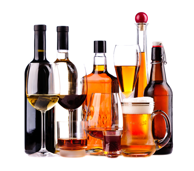 different bottles and glasses of alcoholic drinks isolated on a white background