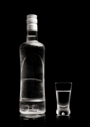 Close-up view of bottle and glass standing of vodka isolated on black
