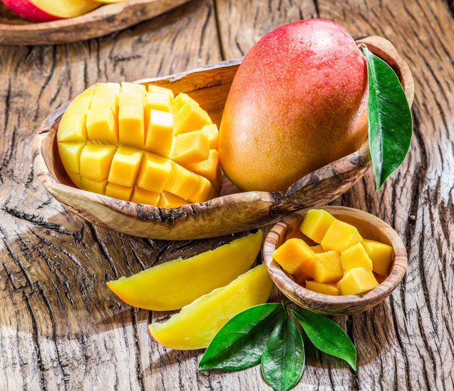 Mango fruit and mango cubes on the wooden table.
