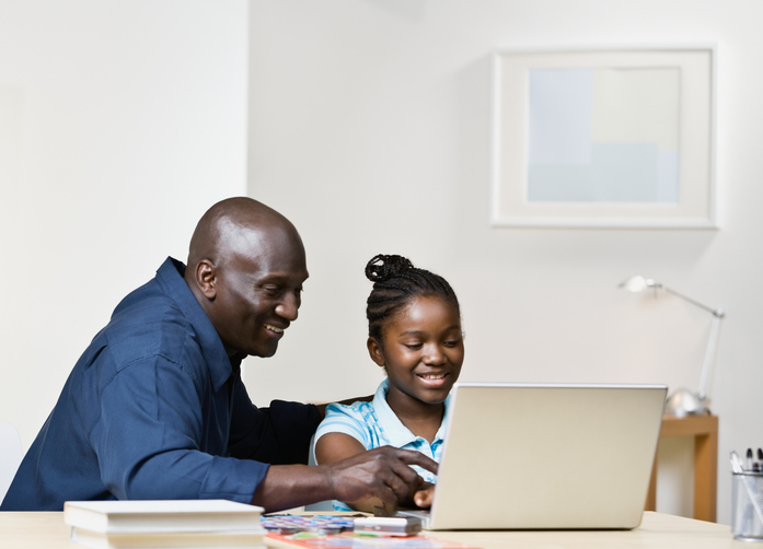 African American father and daughter on laptop