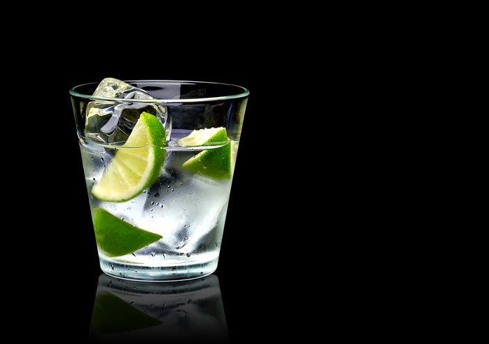 Vodka lime with ice in rocks glass on black background including clipping path