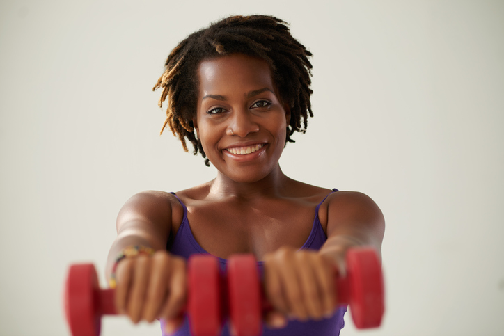 Cheerful healthy young woman exercising with dumbbells