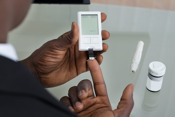 African American man testing blood sugar diabetes