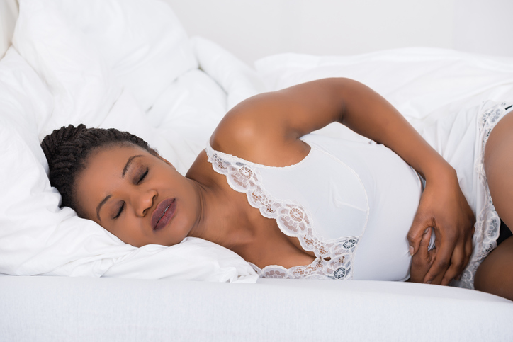 African American woman in bed stomach ache