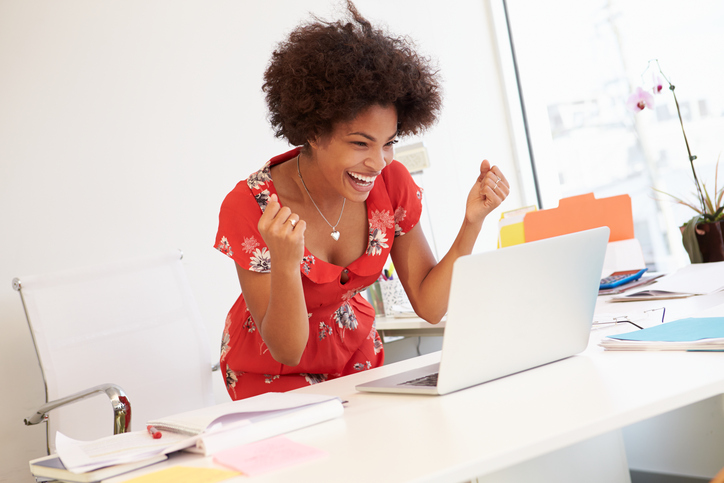 excited African American woman at work on laptop