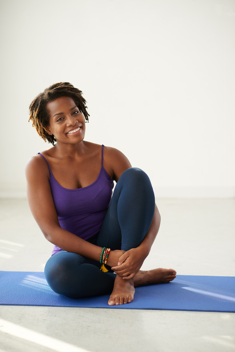 Happy African American woman exercising on yoga mat