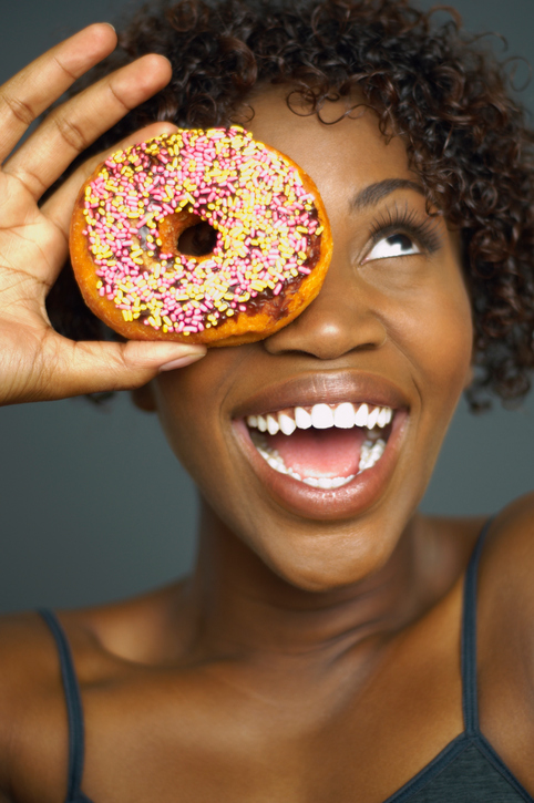 African American woman smiling with donut