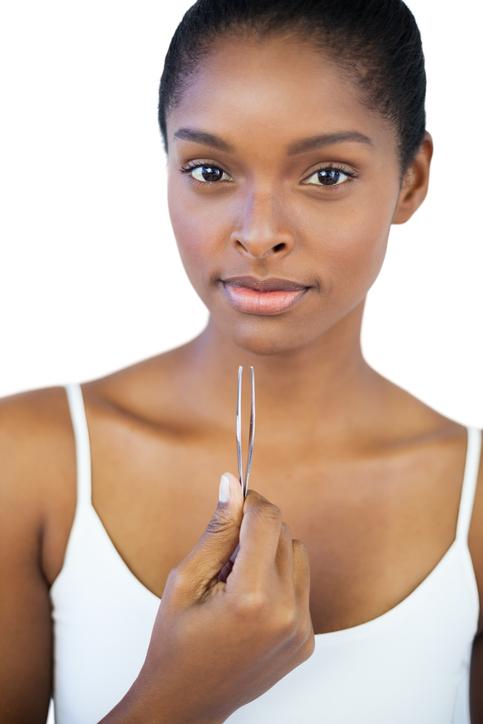 African American woman holding tweezers