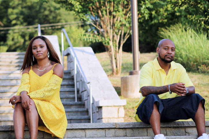 African American couple sitting apart outside