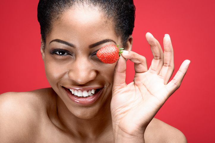 African American woman holding strawberry by eye