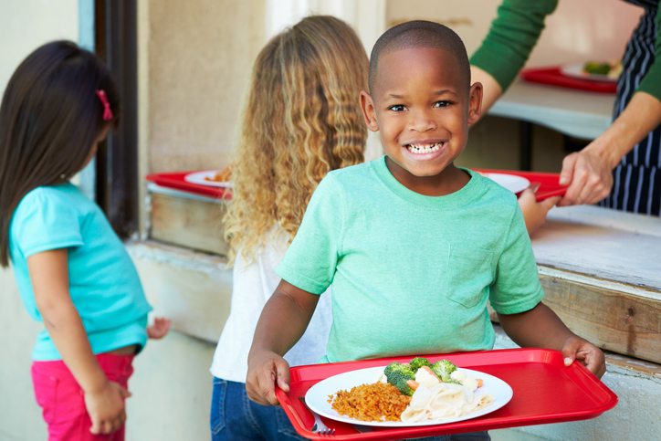 African American boy eating school lunch