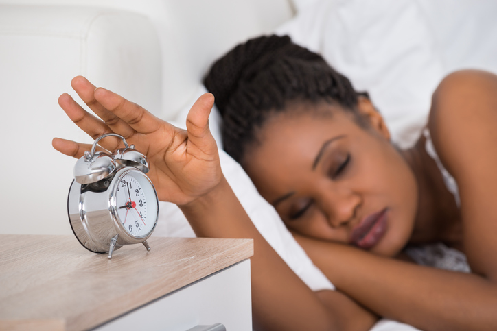 African American woman sleeping in bed hitting alarm