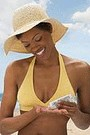 african american woman putting on sunscreen