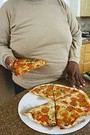 obese man eating whole pizza