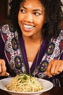 african american woman eating pasta