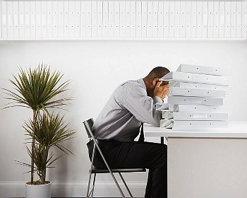 A man resting his head on his desk