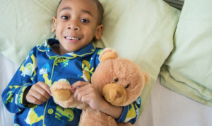 A little boy holding his teddy bear and wearing his pajamas in his bed