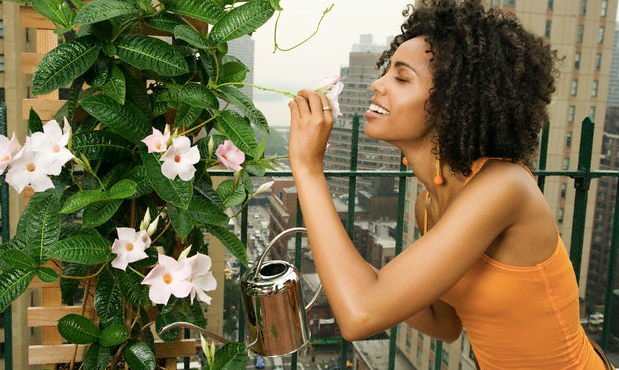 A woman smelling a flower as she waters a plant on her balcony