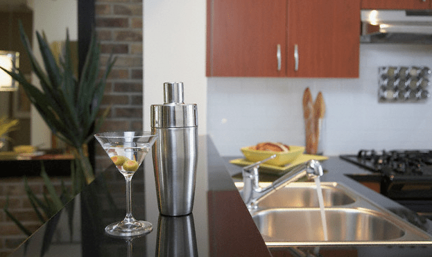 A martini glass and a silver shaker sitting on a kitchen countertop