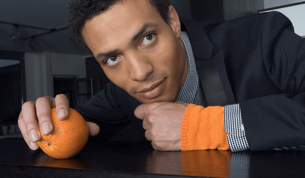 A man leaning on a desk and touching an orange