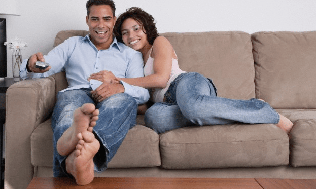 A couple on the sofa, the man holding a tv remote