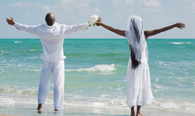 black groom and bride at beach