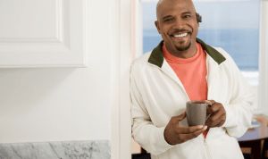 A smiling man holding a cup of coffee in his kitchen