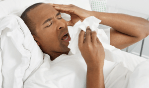 A man holding tissue as he sneezes while lying in his bed